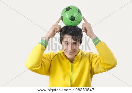 Young Man Holding Up A Football Ball.