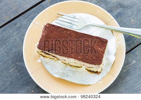 Tiramisu cake on wooden table background