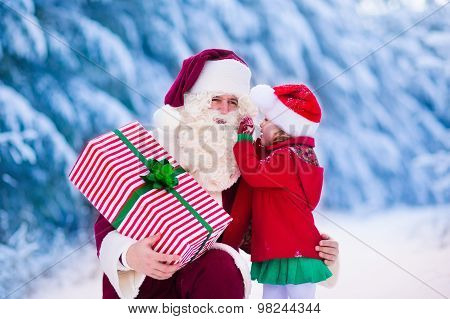 Santa Claus Talking To Little Girl In Snowy Park