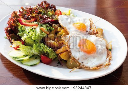 Close Up Of Fried Potatatoes With Mixed Salad And Fried Eggs