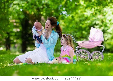 Mother And Kids Enjoying Picnic Outdoors