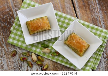 Pistachio baklava in white bowls on checkered cloth on rustic wooden surface
