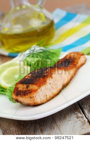 Grilled salmon with lemon and side salad on white plate