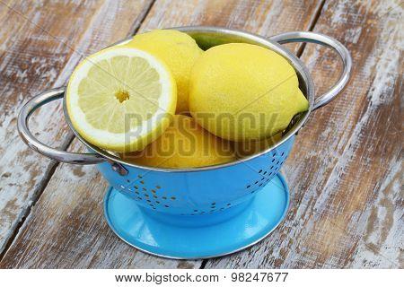 Lemons in blue colander on rustic wooden surface