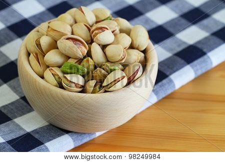 Pistachio nuts in wooden bowl on checkered cloth