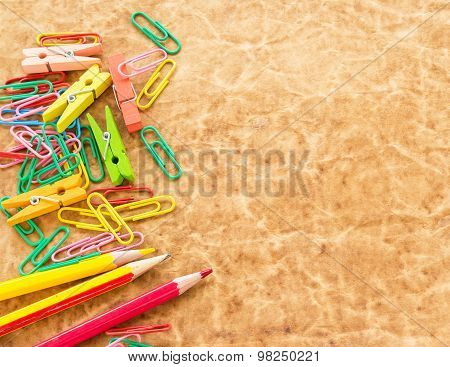 Colorful Pencil And Paperclips On Old Paper Background