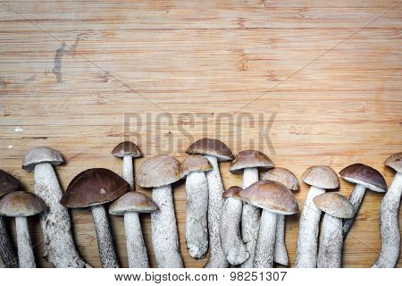 Boletus Edulis, Mushrooms On The Wooden Table In A Raw. Space For Your Text Above.