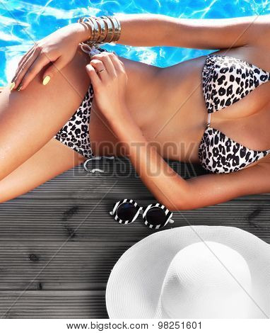 Summer holiday fashion concept - tanning woman with sun hat and sunglasses at the pool on a wooden pier
