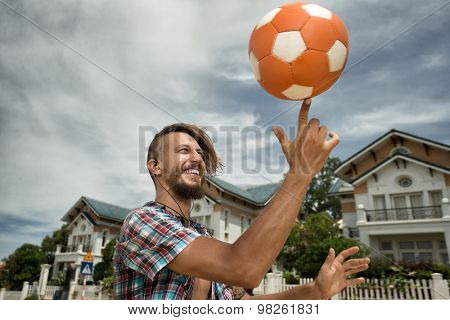 Attractive man spinning a ball on his finger on the street