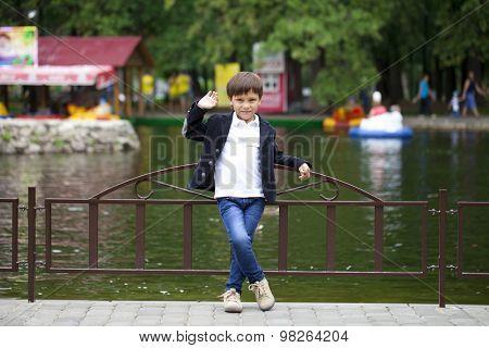 Full length portrait of a little boy in the summer park