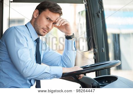Handsome young driver is sitting at steering wheel