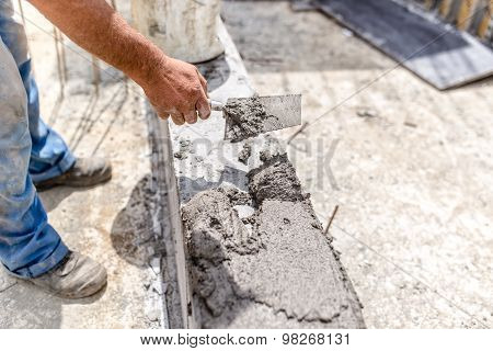 Construction Industry Worker Using A Putty Knife And Leveling Concrete On Concrete Pillars