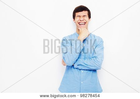 Young hispanic man wearing jeans and glasses standing with hand on his chin and laughing out loud against white wall - humor concept