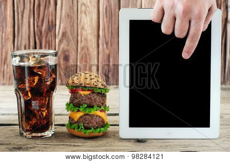 On A Wooden Table Burger, Cola With Ice And White Tablet Concerns The Men Hand
