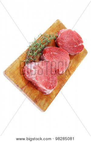 fresh red meat : three raw beef fillet chops on wooden board with thyme twig ready to prepare . isolated over white background