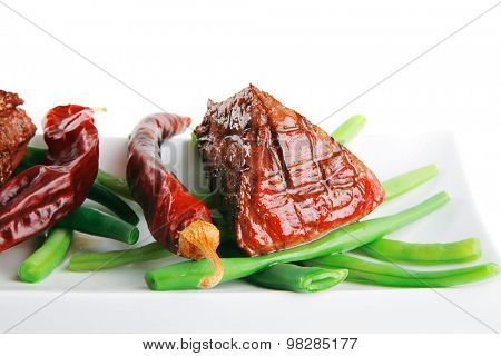 served grilled beef veal fillet entrecote on a white plate with peppers and green peas on long plate isolated on white background