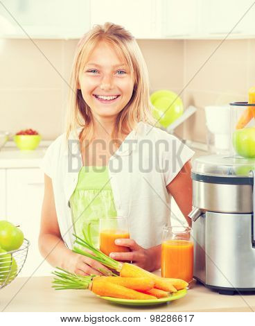 Happy Girl drinking fresh carrot and apple juice. Juice Extractor. Healthy eating concept, vitamins.