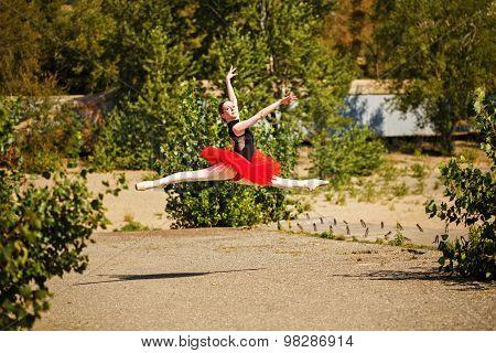 Ballerina In Red Tutu Dancing In Park. Grande Pas Des Chat