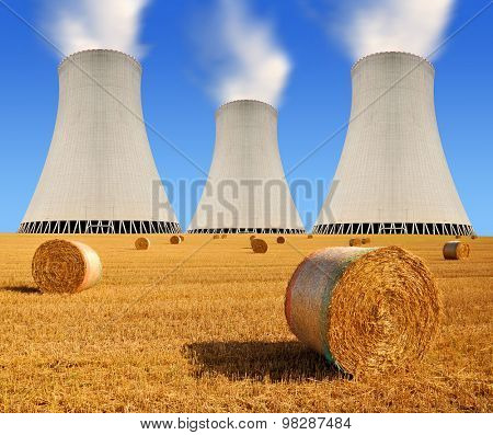 Bales of straw on the field in the background cooling tower nuclear power plant