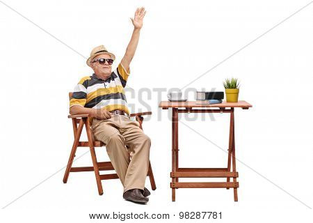 Cheerful senior gentleman sitting at a coffee table and waving with his hand isolated on white background