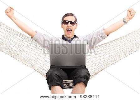 Delighted businessman working on laptop and gesturing success seated in a hammock isolated on white