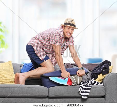 Upset guy trying to pack a lot of clothes into one suitcase on a gray sofa at home shot with tilt and shift lens