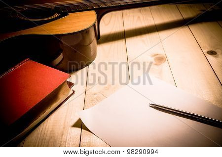Guitar With Red Book And Pen On A Wooden Table, Vintage Style. .