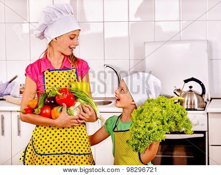 Child holding vegetable at kitchen. Kids cooking at home