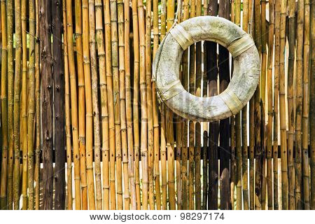 old lifebuoy at the bamboo fence