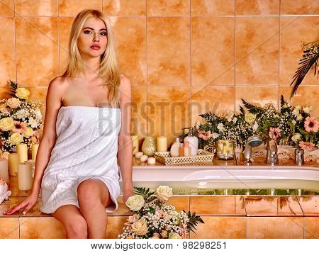 Blonde woman relaxing at flower water spa. Spa and sauna