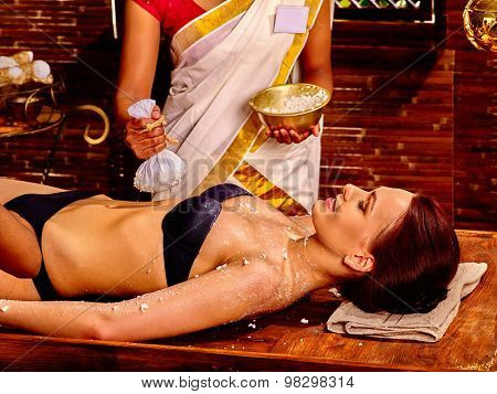 Woman having ayurvedic massage with pouch of rice. Spa resorts in India