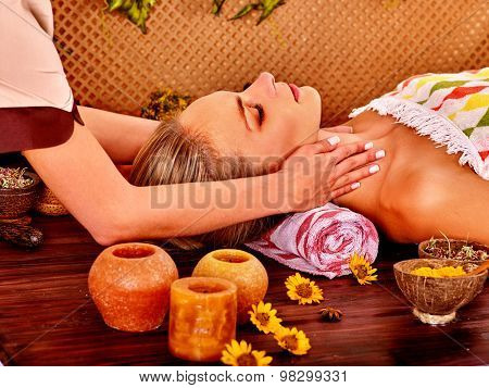 Woman getting facial massage in tropical beauty spa. Rest and recovery