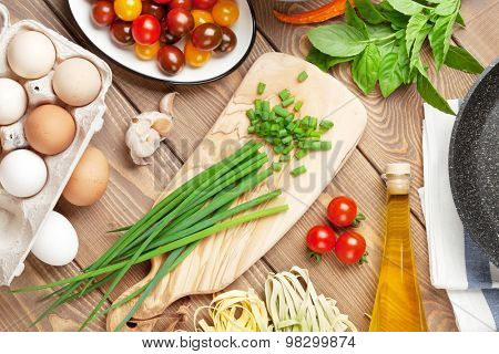 Pasta cooking ingredients and utensils on wooden table. Top view
