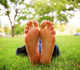 stock photo of human toe  - smiley faces on a pair of feet on all ten toes in a park setting - JPG
