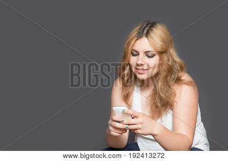 Studio shot of attractive long haired teenage girl smiling and using her smart phone. All is on the gray background. All potential trademarks and buttons are removed.