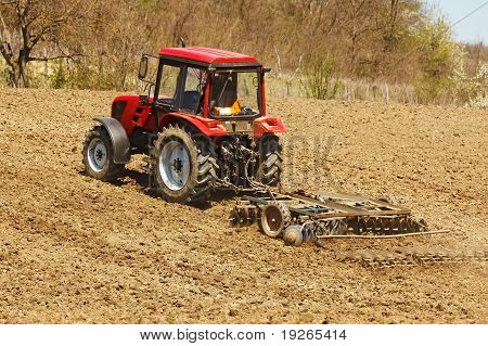 Tractor With Disk Harrow And Rake