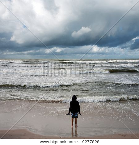 Man looking into stormy sea