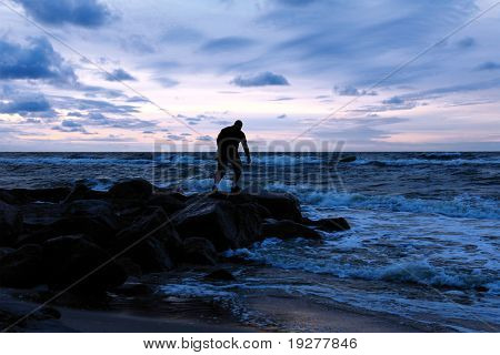 Man standing on a stony sea shore and observing sunset