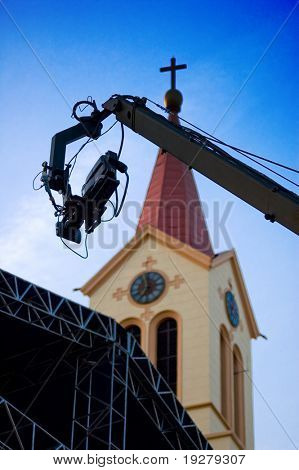 TV camera on the crane and with the church in the background