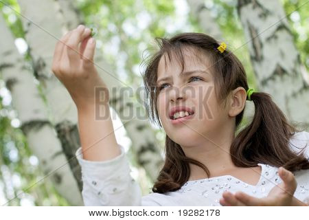 Cute brunette girl standing outdoor holds found larva