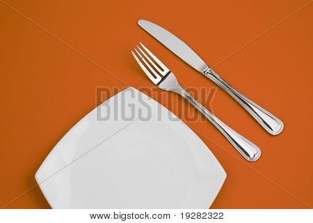 Knife, square white plate and fork on orange background