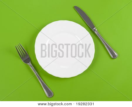 Knife, white round plate and fork on green background