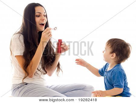 Mother and son have fun with soap bubble together isolated on white