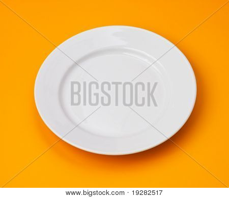 White round plate on orange background