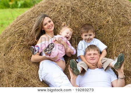 Happy family has fun in haystack together