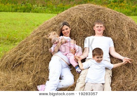 Happy family has fun in haystack together