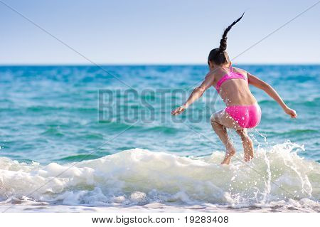 Girl jumping over sea wave. Summer, vacation