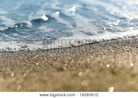 Sand beach and sea foam macro with narrow focus background