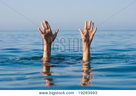 two hands of drowning man in sea asking for help