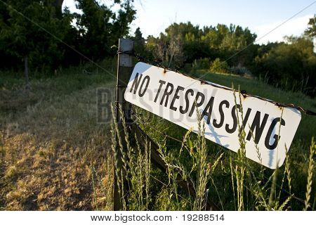 No Trespassing sign posted on barb wire fence